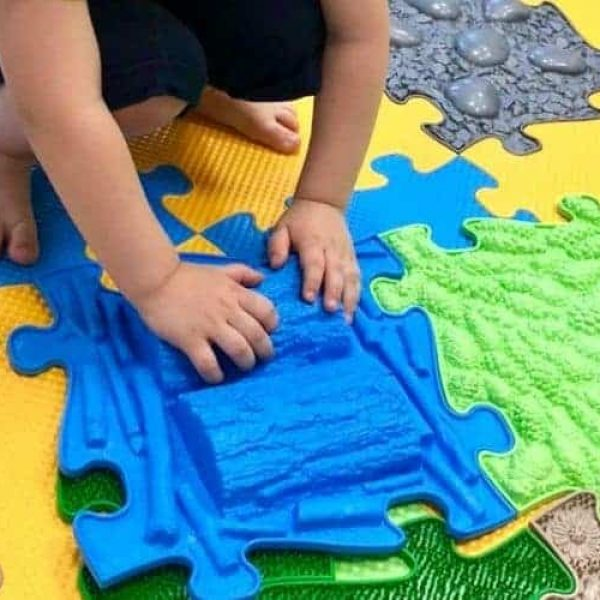 Child playing with Muffik sensory playmat Blue tile