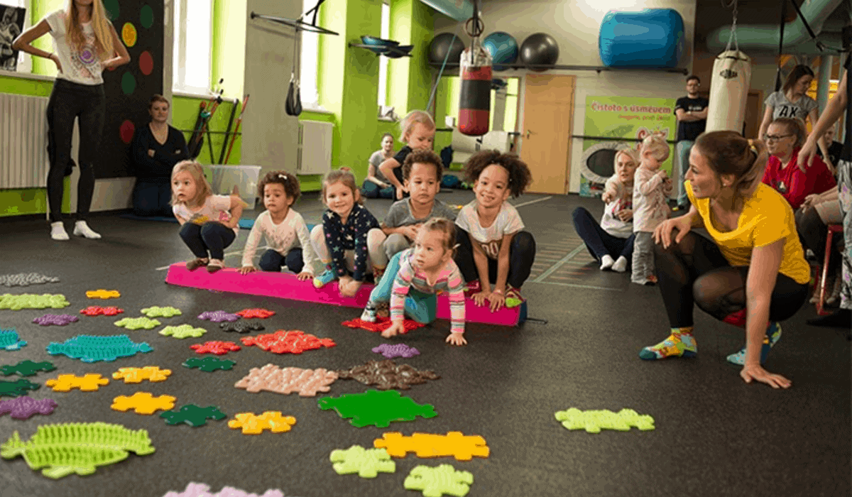 Happy children play with muffik sensory play mats with teachers during a session in a nursery