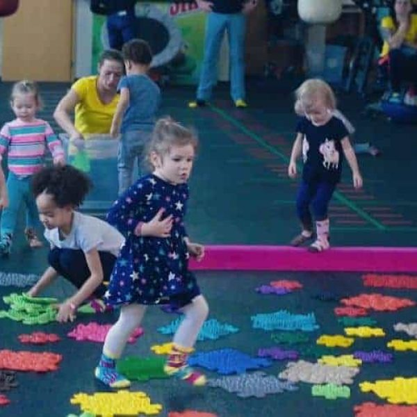 Happy children play on a sensory Muffik path during a session in a nursery